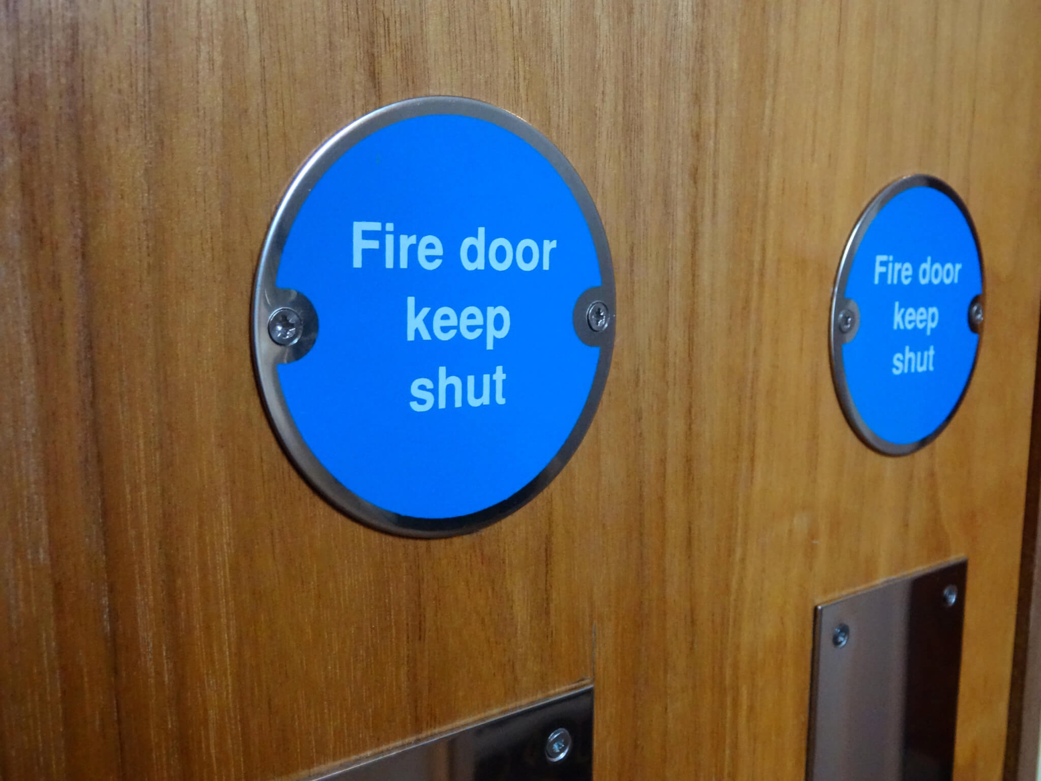 Photo showing a circular blue sign with white writing saying 'Fire Door Keep Shut '.  This safety sign has been screwed onto a wooden fire door.