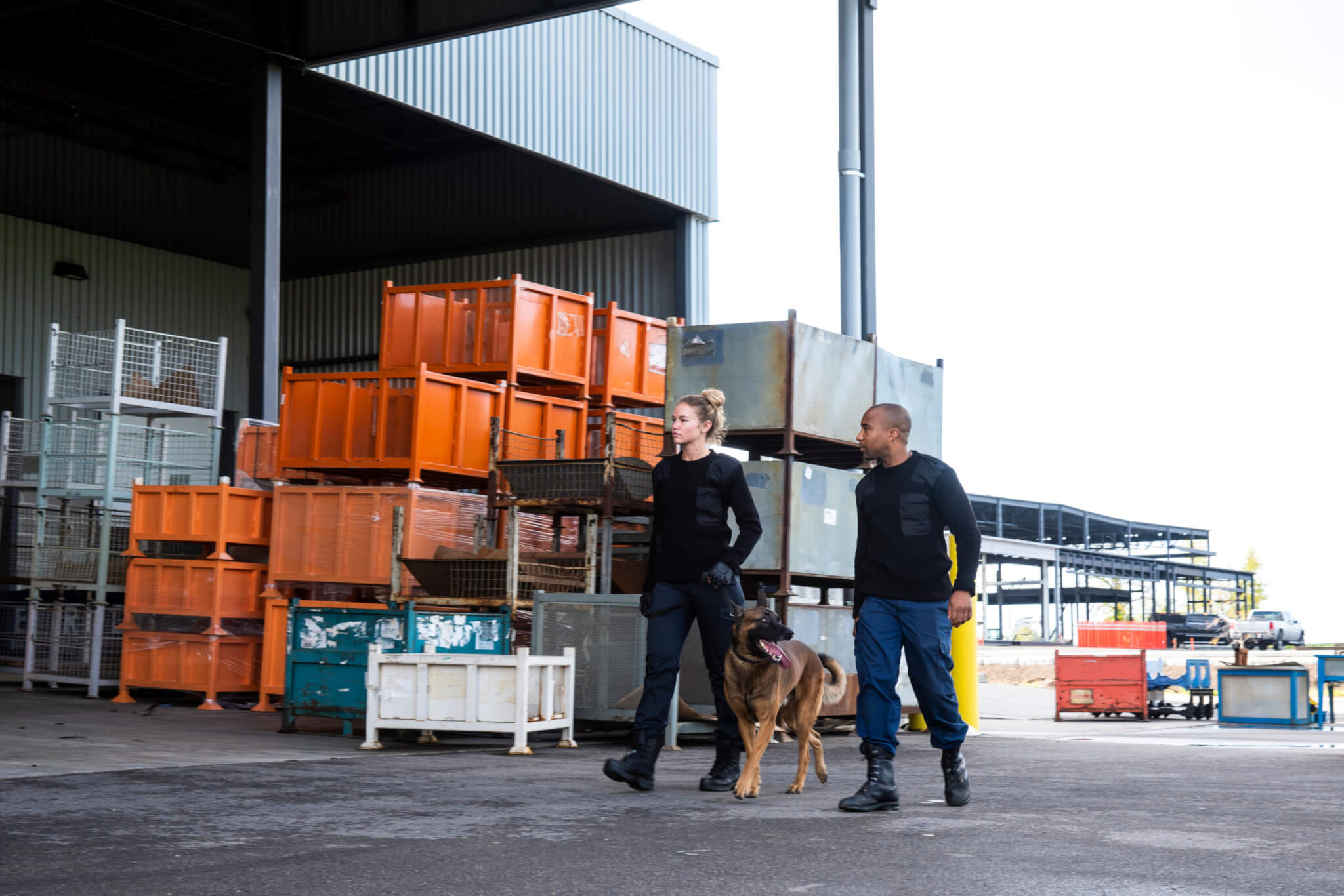 Male and female K-9 security professionals with a Belgian Malinois patrolling outside an industrial building.