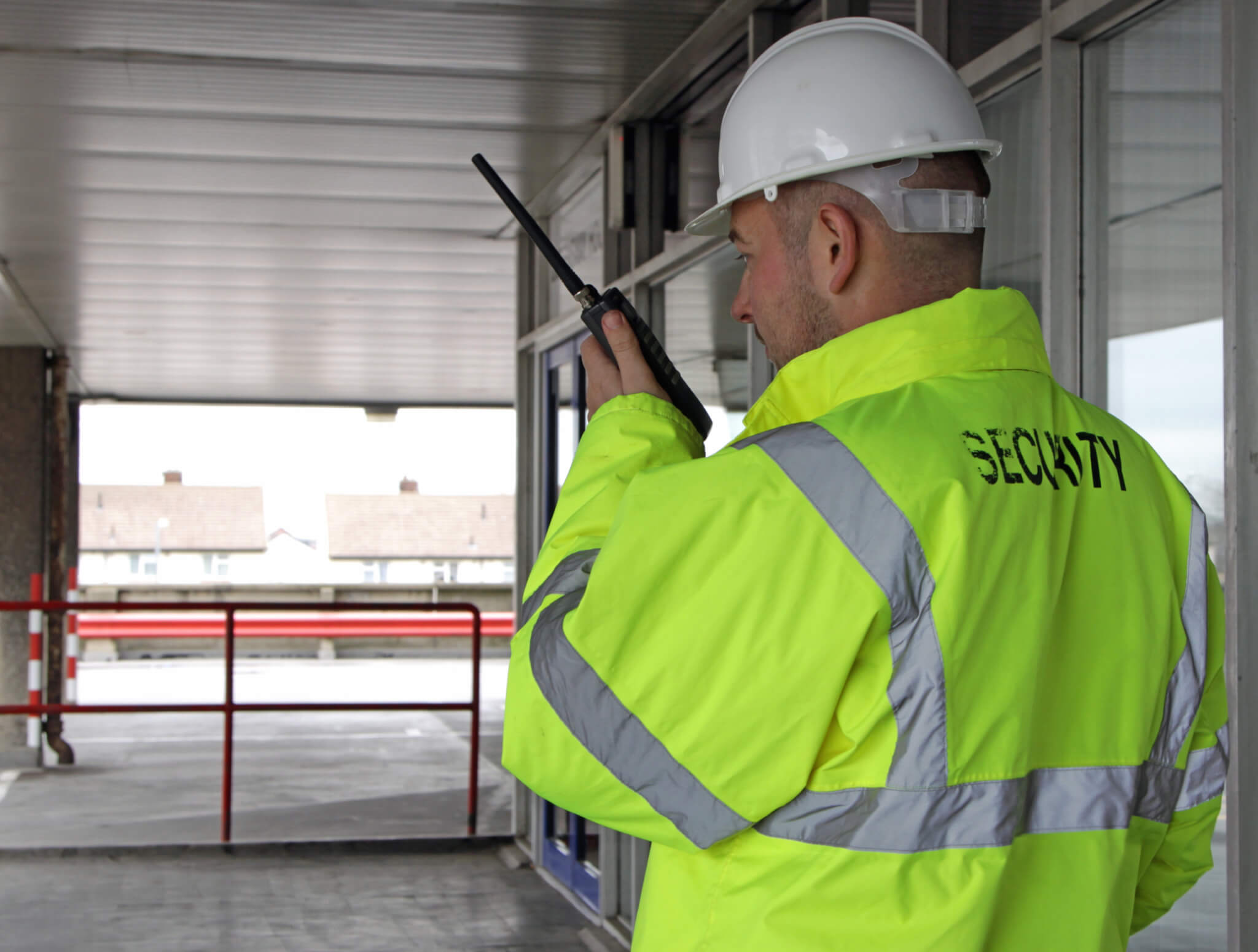 A security man reporting to HQ on a walkie talkie after checking the security of a entrance to a office block.